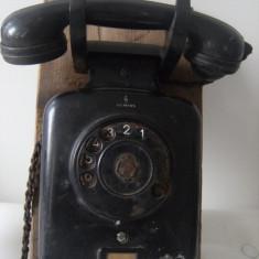 Telefon de perete, foarte vechi, pe suport de lemn, de colectie/decor.
